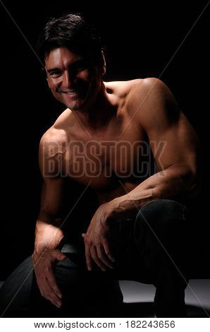 The sexy stud is crouching down with a smile.