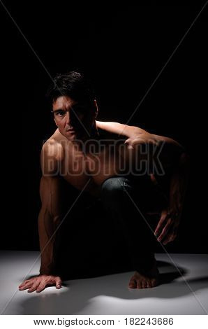 The hot guy is crouched down prepared for battle.