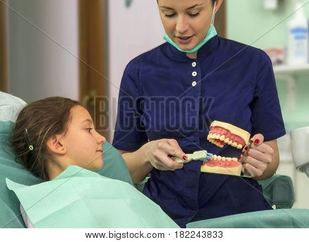 woman dentist explaining brushing procedure to a girl kid using artificial teeth's in clinic studio.