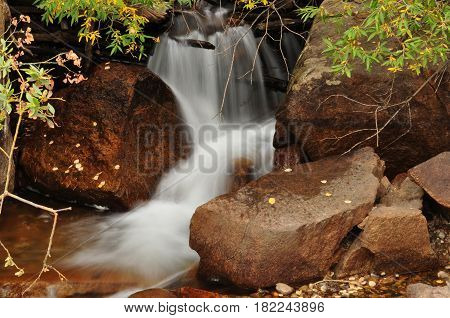 Waterfall cascading slowly over rocks in forest