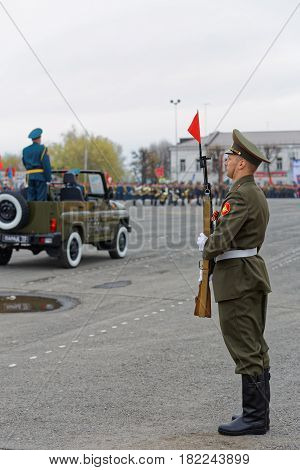 A Russian Soldier With A Rifle Stands In A Solemn Guard At The Victory Day Parade