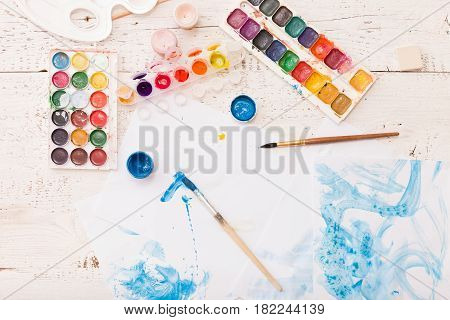 Top view on child's drawings and colorful paints and brushes. Creative ideas creativity and early learning. Education concept.