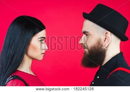 Guy and girl in profile. A guy and a girl in profile on a red background. A guy with a beard in his hat and a brunette girl on a red background
