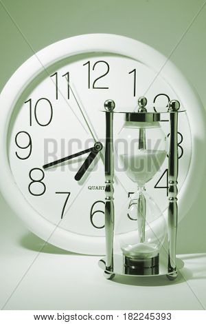 Clock and Hourglass on Light Blue Background