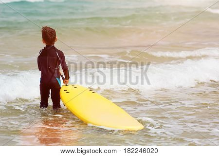 Young boy with bodyboard playing in the surf.