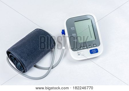 Automatic portable blood pressure machine with arm cuff isolated on white, shot from above.