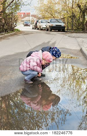 Two children sit on the asphalt road and look at their reflection in a puddle