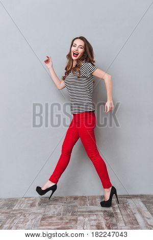 Full length portrait of a happy woman  walking in studio and looking at the camera over gray background. Side view. Vertical image