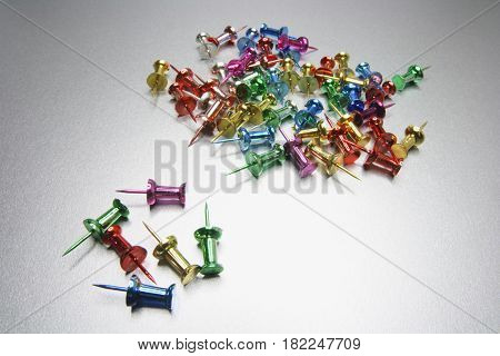 Two Piles of Push Pins on Light Grey Background