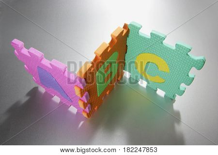 Pieces of Foam Alpohabet Puzzle on Seamless Background