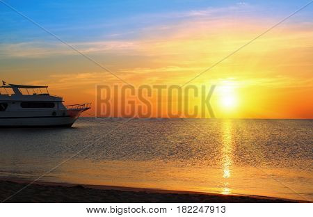 ship at anchor on background of sunrise over sea