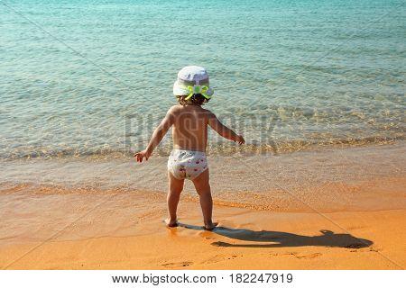 little girl on sand beach near sea