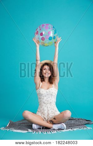 Portrait of a happy cheerful summer girl in straw hat sitting on a blanket and holding beachball above her head isolated over blue background