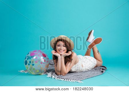 Portrait of a cheerful smiling summer girl in straw hat laying on a blanket with beachball isolated over blue background