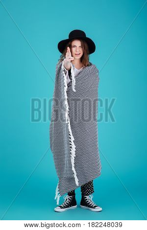 Full length portrait of a funny young woman in hat covered in blanket making shooting gesture with fingers isolated over blue background