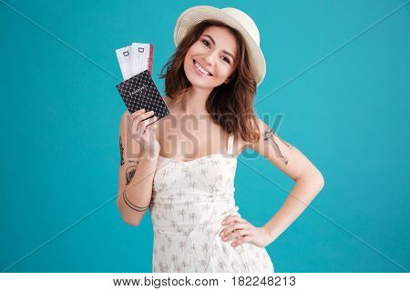 Portrait of a happy smiling young girl holding passport and travelling tickets isolated over blue background
