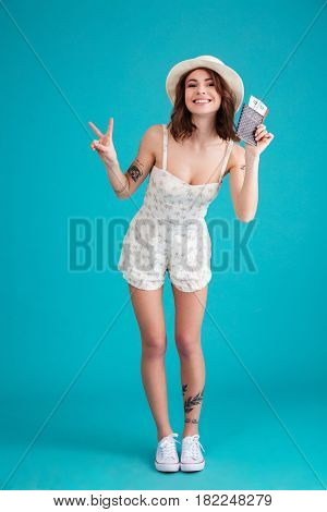 Full length portrait of a happy satisfied young traveller woman in beach hat standing and showing passport with tickets isolated over blue background