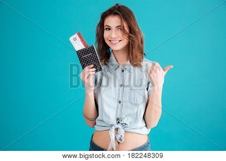 Portrait of a smiling satisfied young woman in summer clothes holding passport with plane tickets and showing thumbs up gesture isolated over blue background
