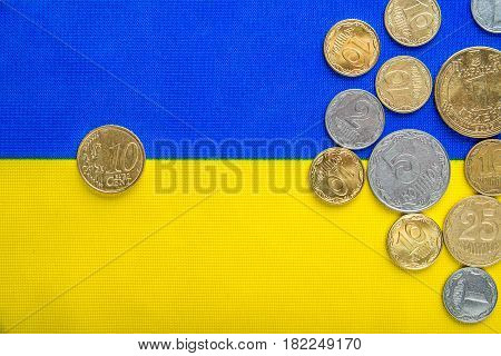 Ukrainian national coins and ten euro cents against the background of the national flag. Eurovision currency