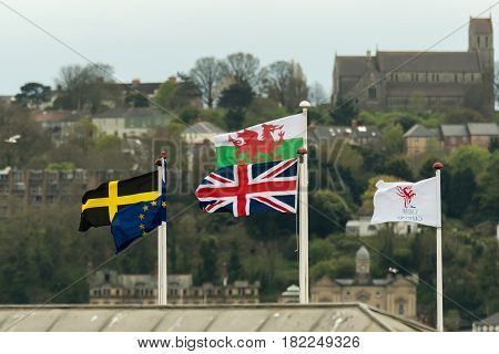 Flags flying at Cardiff Bay, in front of St. Augustine's Church. Flag of Saint David the European Union Wales the UK and Cardiff with Penarth in the background