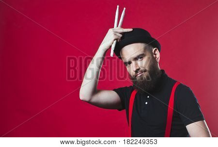 The drummer on the background. Bearded drummer on a red background. Bearded guy on a red background. Cheerful bearded man. The guy in the hat