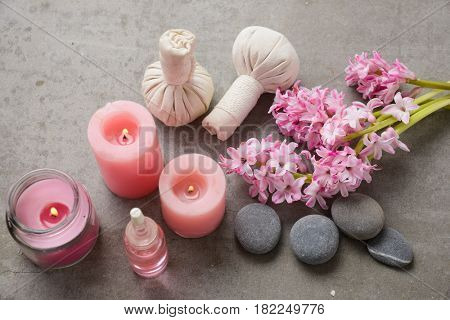 spa setting with Hyacinth flowers,ball,candle ,oil,stone on gray background
