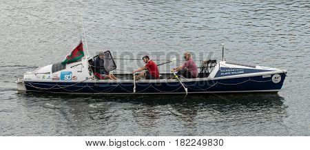 CARDIFF UK - APRIL 14 2017. Talisker Whiskey Atlantic Challenge boat with crew. Rowers and coach training for Atlantic crossing on board ocean-going rowing boat on lake in Cardiff Bay Wales