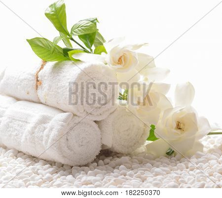 Branch gardenia and rolled towel on pile of white stones,