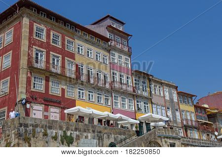 PORTO, PORTUGAL - APRIL 17, 2017: Tourists and locals enjoy the Ribeira in the Douro River bank near the Dom Luis I Bridge, Porto, Portugal.