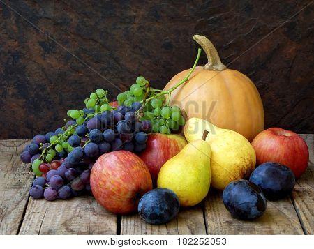 Still Life Of Autumn Fruits: Pumpkin, Grape, Apple, Pear, Plum On A Wooden Background. Selective Foc
