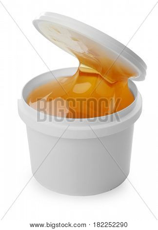 Plastic bucket with sugaring paste on white background