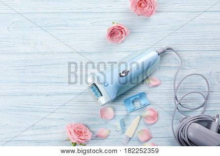 Modern epilator with accessories and flowers on wooden background