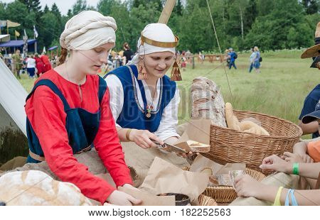 RITTER WEG MOROZOVO APRIL 2017: Festival of the European Middle Ages. Women put pate on hearth bread at the thematic medieval fair