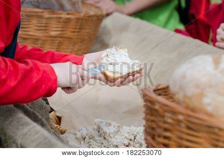 Woman put pate on hearth bread . Open air medieval festival.