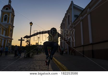 Granada Nicaragua - April 4 2014: Boy skateboarding in a street of the colonial city of Granada in Nicaragua at sunset with a tower of the Granada Cathedral on the background