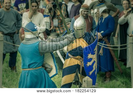 RITTER WEG MOROZOVO APRIL 2017: Festival of the European Middle Ages. Medieval joust knights in helmets and chain mail battle on swords with shields in their hands.
