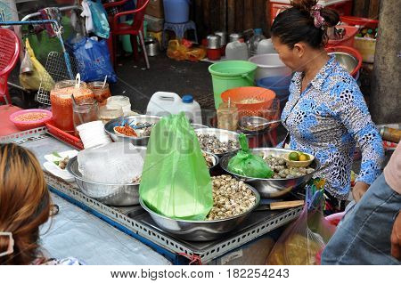 Woman Selling Street Food, Sea Snails And Other Sea Food With Vegetables In Saigon
