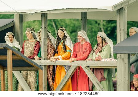 RITTER WEG MOROZOVO APRIL 2017: Ladies in medieval clothes stand in bed watching the tournament of Knights. Historical reconstruction.