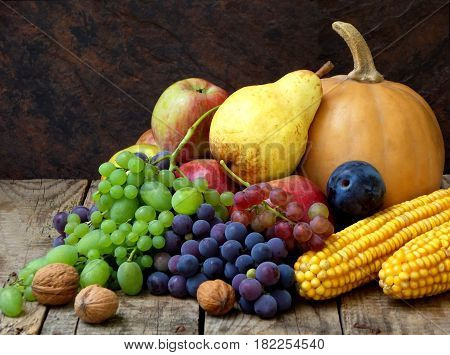 Still Life Of Autumn Fruits And Vegetables Like Grapes, Apples, Pears, Plums, Pumpkin, Corn Nuts On
