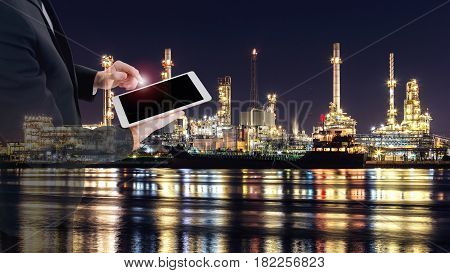 Double exposure business man in suit holding tablet on hand. Oil tankers and oil refinery in Background.