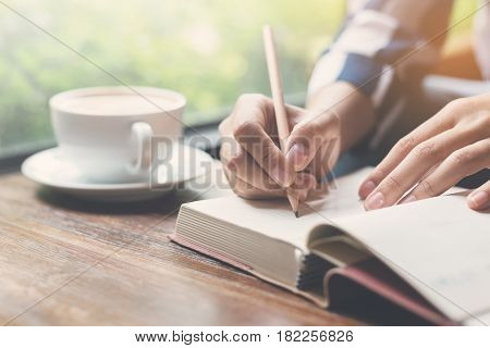 Closeup Woman writing on notebook with pencil. A cup of coffee on wooden table.