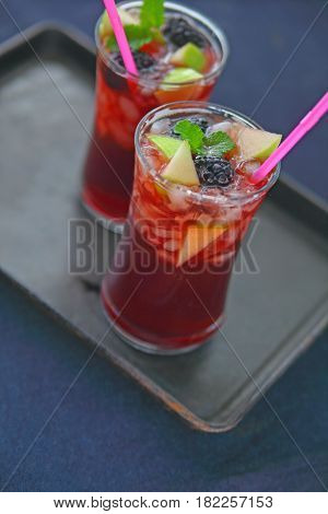 Two chilled sangria cocktails with fresh blackberries and apple pieces on a dark metal tray with copy space