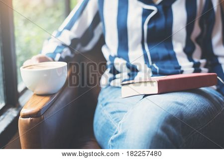 Focus on book. Relaxed Woman sitting on leather sofa with window.