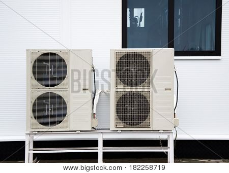 Two condensers of air conditioners standing on the ground in front of facade of the modern building