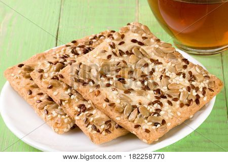 crispy bread with seeds of sunflower, flax and sesame seeds with a cup of tea on a green wooden background.