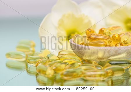 Fish oil capsules in wooden spoon with flower background. Fish oil dietary supplement. Pharmaceutical vitamins supplement.