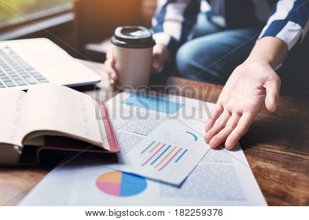 Business woman hands holding cup of coffee. Graph financial diagram documents with laptop on wooden table at the office.