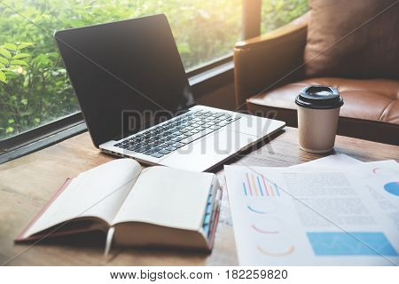 Closeup of laptop with cup of coffee notebook graph financial diagram documents on wooden table.