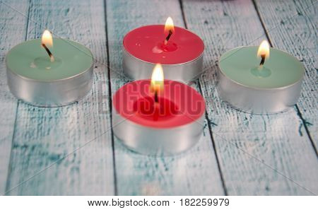some colourful tea lights on a wooden background