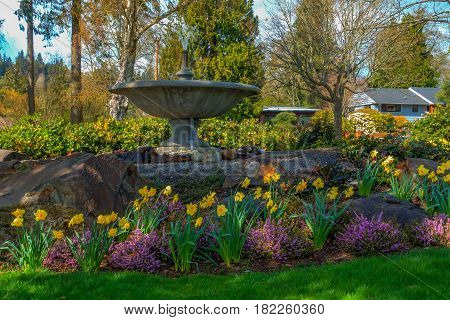 A view of Spring flowers and a cement fountain in Normandy Park Washington. HDR image.